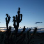 The sun rises into the early in Arizona as the Moon and Venus hang in the sky.